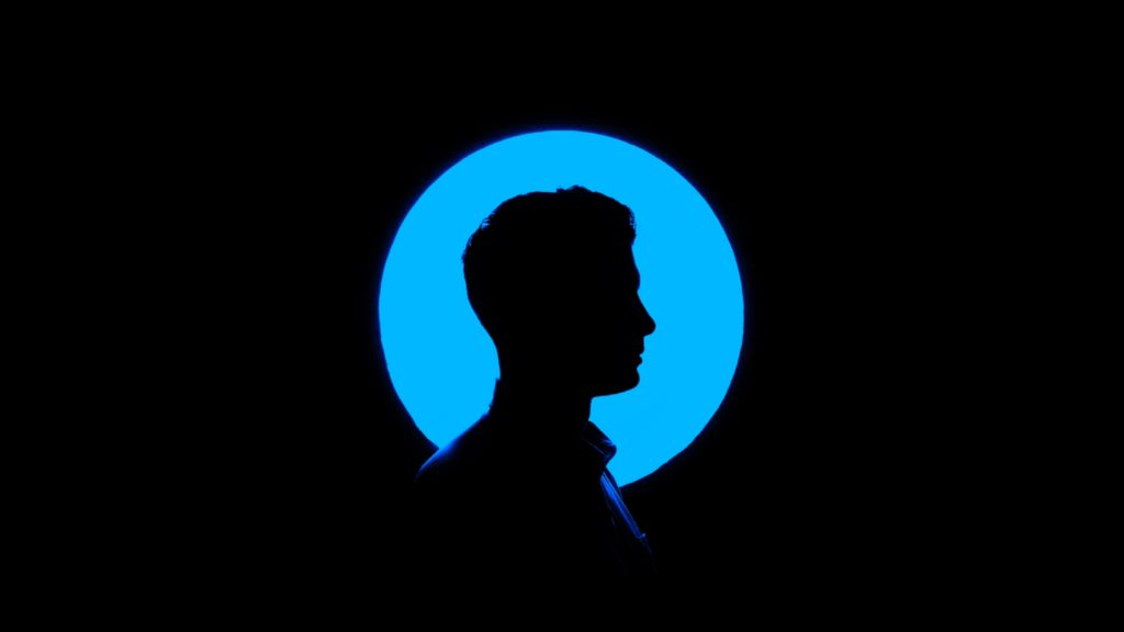 Person i profil mot blå och svart bakgrund.