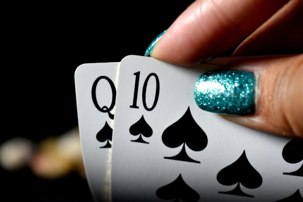 Person håller upp två spelkort. Korten föreställer spader dam och spader tio.